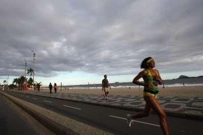 mujer trotando a orillas de la playa